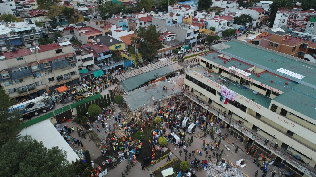Mexican rescue teams look for people trapped in the rubble at the Enrique Rebsamen elementary school in Mexico City on September 20, 2017. At least 21 children were killed and about 30 children are still missing at the school.