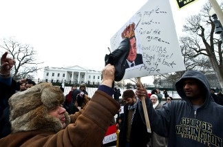 A man hits a picture of Egyptian President Hosni Mubarak with his shoe as people demonstrate in support of the Egyptian people's protests against Mubarak's regime in front of the White House on Jan. 29, 2011.