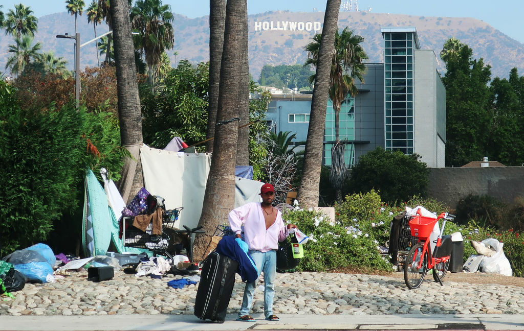 A man stands in front of a homeless encampment, with the Hollywood sign in the background