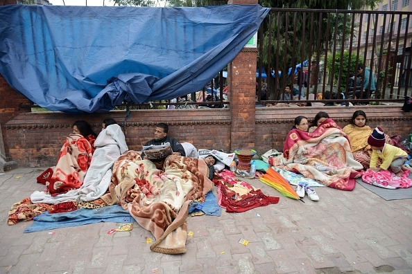 Nepalese residents rest as they gather on a pavement in Kathmandu on April 26, 2015, a day after an earthquake hit.