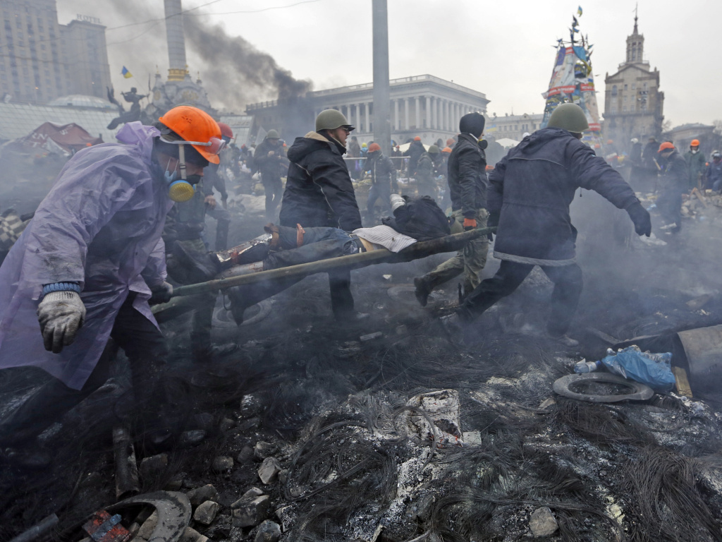 An injured man is carried away Thursday after more clashes between anti-government protesters and police in Kiev.