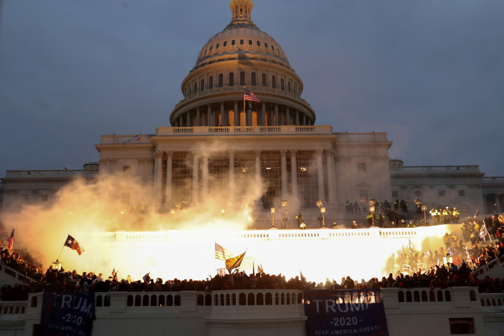 An explosion caused by a police munition is seen while supporters of then-President Trump gather in front of the U.S. Capitol building on Jan. 6.