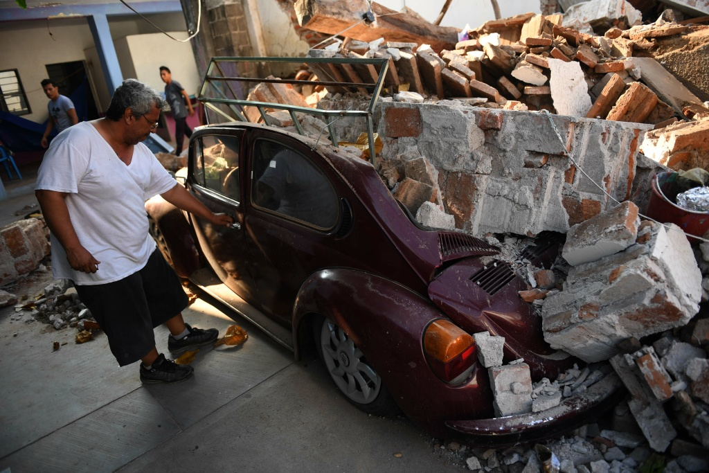 A man inspects his car, which was crushed by debris from his house during the powerful earthquake that struck Mexico's Pacific coast late on September 7, 2017 in Juchitan de Zaragoza, Mexico.