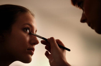 A model has eye make-up applied in preparation for The Royal College of Art Fashion Show on June 10, 2010 in London, England.