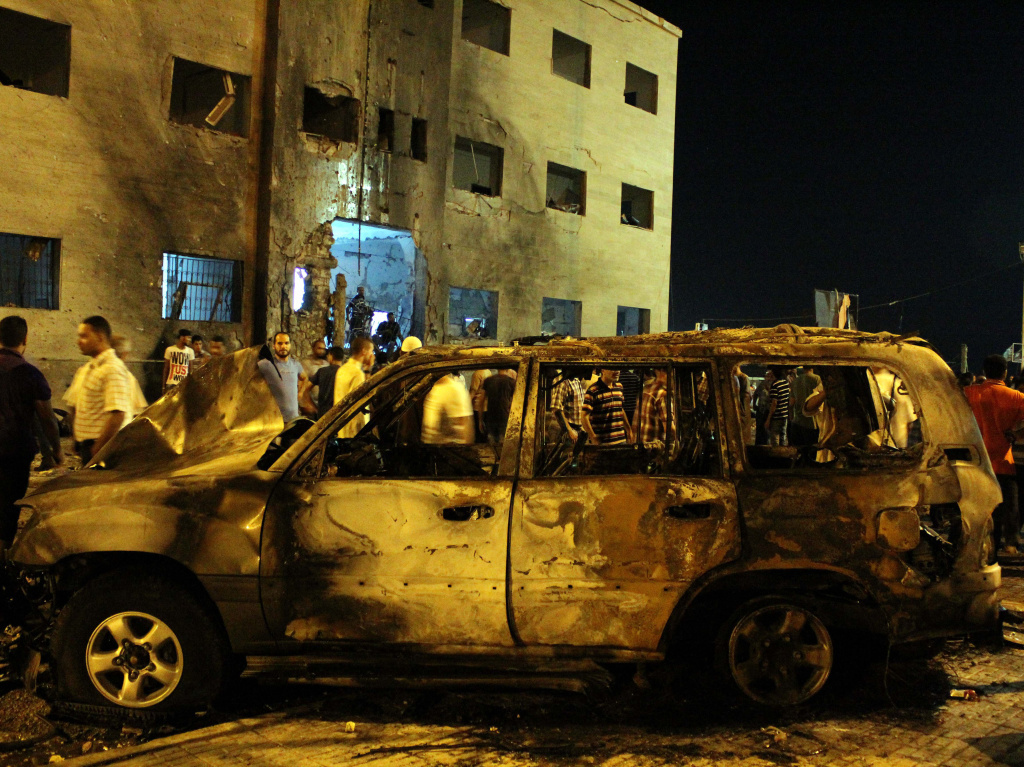 Libyans gather near a burned-out vehicle after an attack outside the courthouse in Benghazi the day after more than 1,000 inmates escaped during a prison riot.