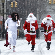 Revelers dressed as Santa Claus run as the arrive at Tompkins Square Park to take part during the annual SantaCon bar crawl event on December 14, 2013 in New York City.