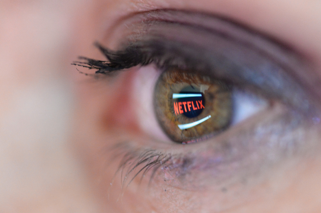 In this photo illustration, the Netflix logo is reflected in the eye of a woman.