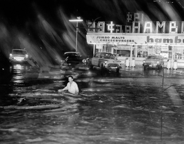 1938: People walk along the flooded L.A. River near the Dayton Avenue Bridge. In the background, a railroad bridge hangs in a twisted heap after one of the pilings has collapsed. (Photograph courtesy of the Los Angeles Public Library)