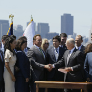 California Gov. Jerry Brown, right, shakes hands with former Gov. Arnold Schwarzenegger, left, after signing a climate bill on Treasure Island, Tuesday, July 25, 2017, in San Francisco. Gov. Brown signed legislation keeping alive California's signature initiative to fight global warming, which puts a cap and a price on climate-changing emissions. The Democratic governor was joined by his celebrity predecessor, Arnold Schwarzenegger, who signed the 2006 bill that led to the creation of the nation's only cap and trade system to reduce greenhouse gases in all industries.