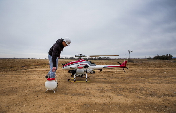 An operator removes sprayer containers a Yamaha RMAX Unmanned Aerial Vehicle (UAV) after a crop dusting test flight at a University of California, Davis, test facility in Arbuckle, California.