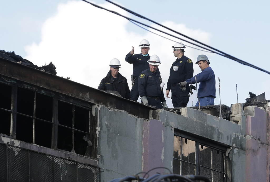 Alameda County Sheriffs and emergency crew workers stand on a roof next to the site of a warehouse fire in Oakland, Calif., Tuesday, Dec. 6, 2016. The fire erupted Friday, Dec. 2, 2016, killing dozens.