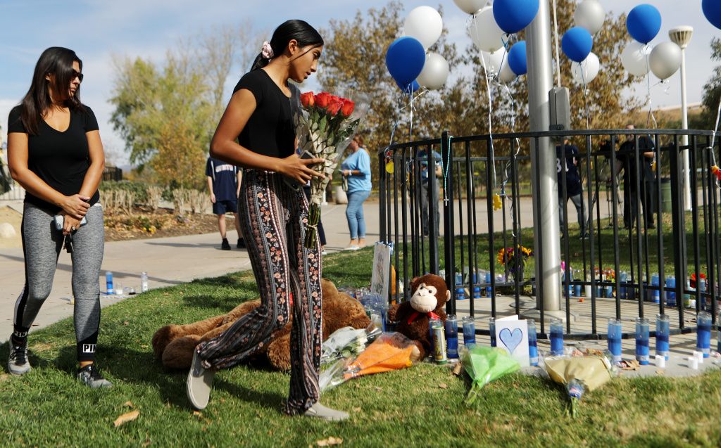 A student brings flowers to a makeshift memorial in Central Park to victims of the shooting at nearby Saugus High School on November 15, 2019 in Santa Clarita, California.