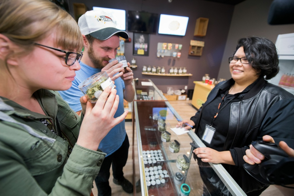 Laura Torgerson and Ryan Sheehan, visiting from Arizona, smell cannabis buds at the Green Pearl Organics dispensary on the first day of legal recreational marijuana sales in California, January 1, 2018 in Desert Hot Springs, California.