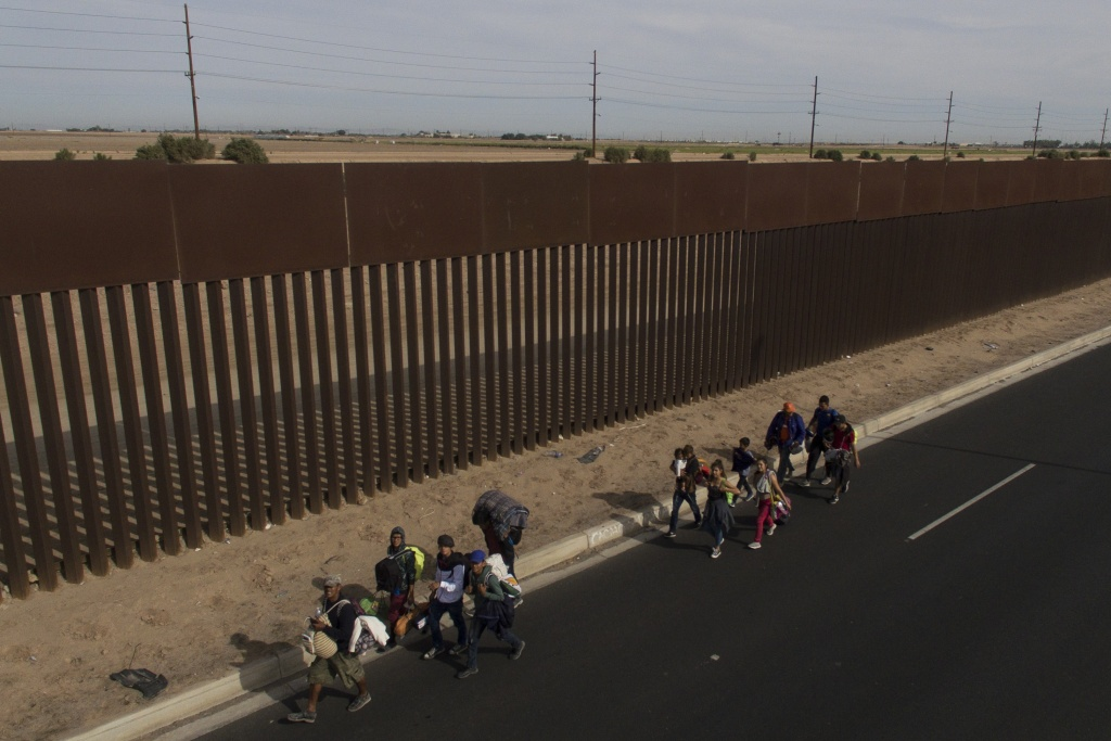 FILE: Central American migrants, mostly Hondurans, moving in a caravan toward the United States, walk along the metal fence on the border between Mexicali in Mexico's Baja California State, and Calexico in California on Nov. 19, 2018.