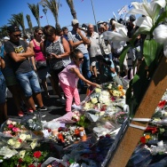 People visit the scene and lay tributes to the victims of a terror attack on the Promenade des Anglais on July 15, 2016 in Nice, France.
