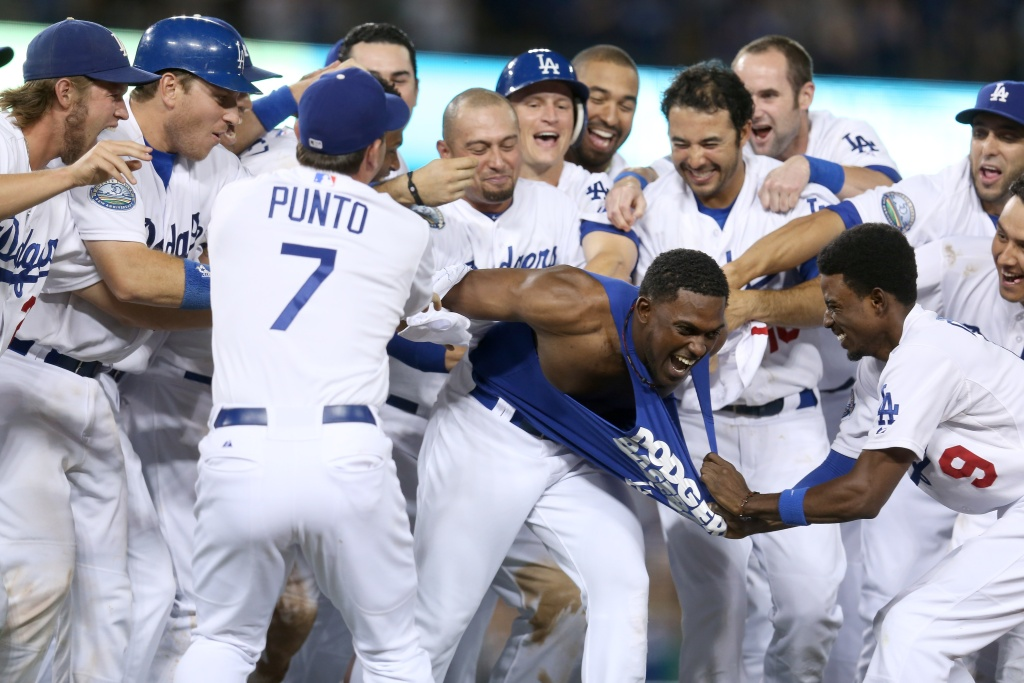 Elian Herrera is mobbed by teammates after his walk off RBI single in the ninth inning to defeat the San Francisco Giants on October 1, 2012 at Dodger Stadium.