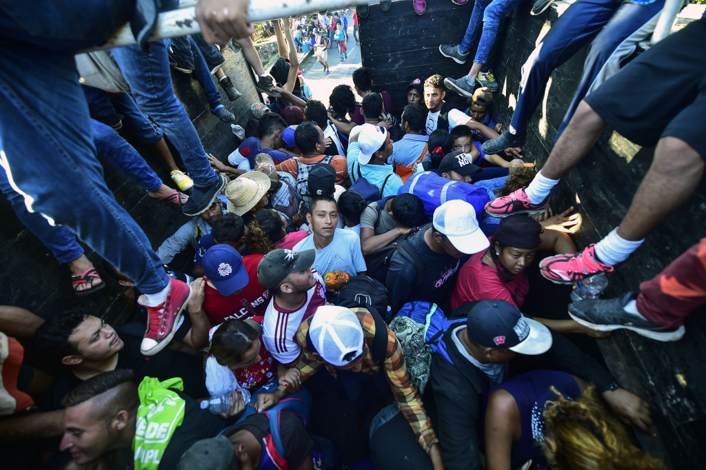 Honduran migrants taking part in a caravan heading to the US, aboard a truck in Metapa on their way to Tapachula, Chiapas state, Mexico on October 22, 2018.