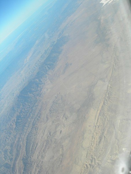 The San Andreas Fault looks like a scar (on the bottom) in the Carrizo Plain area.  This image was taken from the air in 2007.