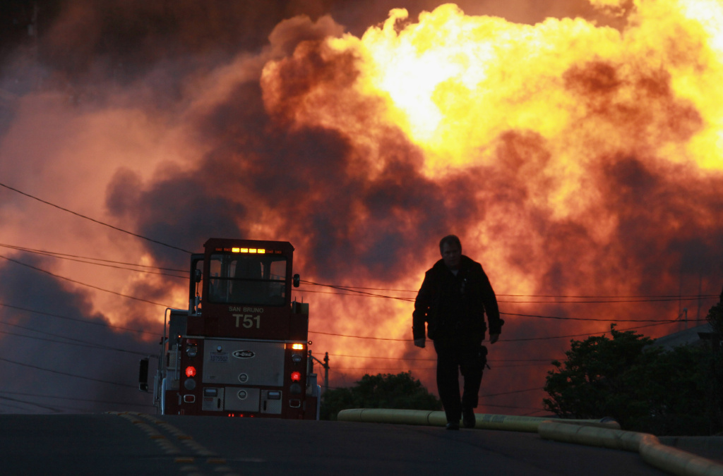 A law enforcement official runs towards a massive fire from a gas pipeline explosion in a residential neighborhood in this September 9, 2010 file photo taken in San Bruno, California. The California Public Utilities Commission is expected to vote Thursday, April 9, 2015, on a record $1.6 billion penalty against PG&E for the deadly explosion.