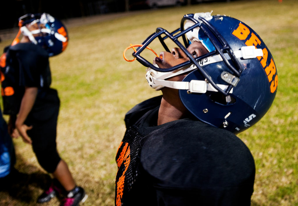Eleven-year-old Robert Turner, a running back and cornerback, looks up as rain comes down during practice.