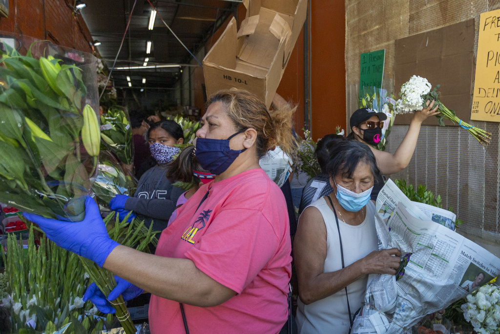 People mingle close to one another as businesses in the flower district in Skid Row reopen in time for Mothers Day on May 8, 2020 in Los Angeles, California.