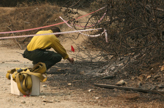 A U.S. Forest Service firefighter uses a flag to mark evidence as he investigates the ignition point of the Station Fire on Angeles Crest Highway September 2, 2009 in La Canada Flintridge, California.