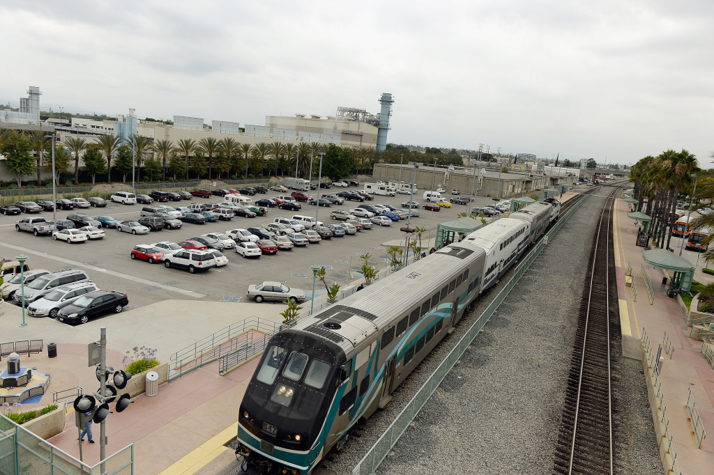 BURBANK, CA - JUNE 24: A Metrolink train stops to pick up passengers at a train station next to the Burbank Water and Power natural gas-fueled power plant on June 24, 2013 in Burbank, California.