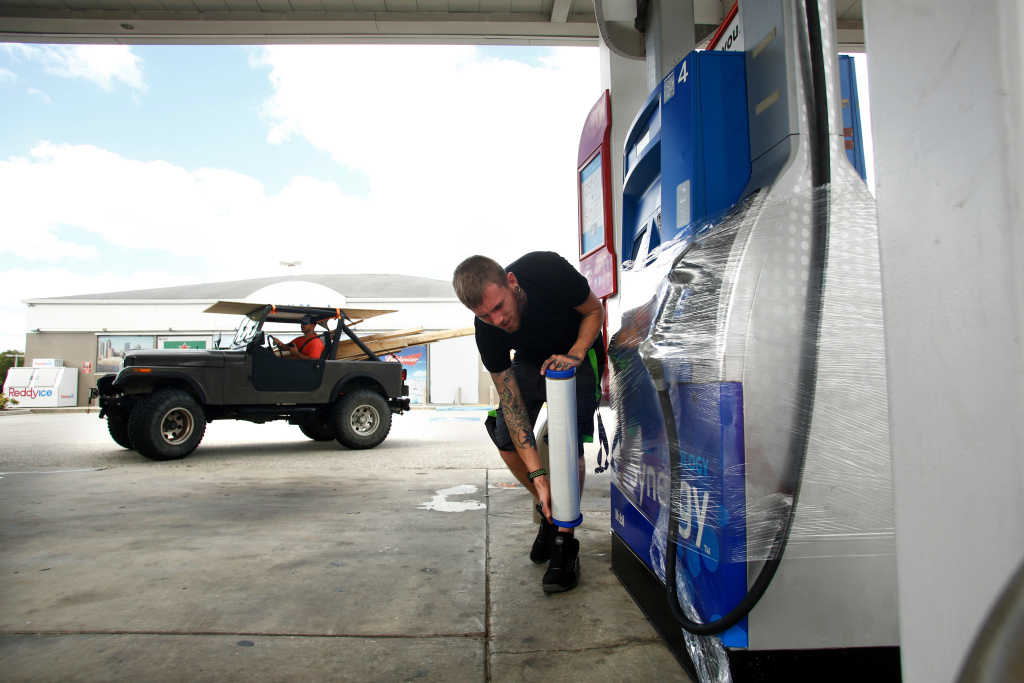 Casey Metcalf wraps up empty fuel pumps at a Mobile station in Tampa, Florida as Hurricane Irma approaches on September 9, 2017.