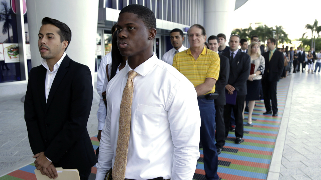 Luis Mendez, 23, left, and Maurice Mike, 23, wait in line at a job fair held by the Miami Marlins at Marlins Park in Miami on Oct. 23, 2013. The nation's unemployment rate slipped to 6.6 percent in January, but employers added only 113,000 jobs to their payrolls last month, the Bureau of Labor Statistics reported Friday.