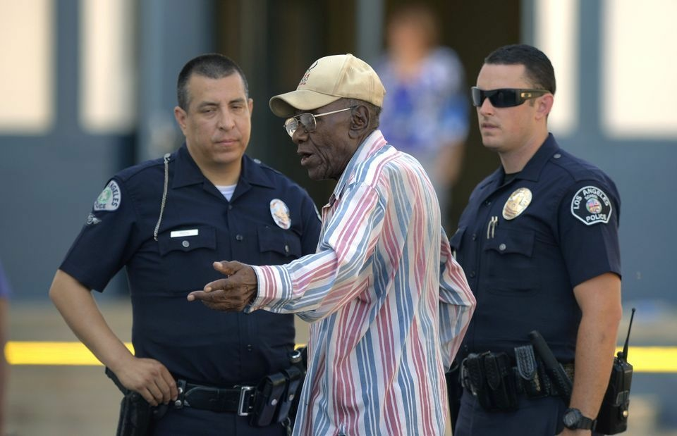 Preston Carter, 100, talks with police officers after police say his car went onto a sidewalk and plowed into a group of parents and children outside a South Los Angeles elementary school, Wednesday, Aug. 29, 2012. Nine children and two adults were injured in the wreck.