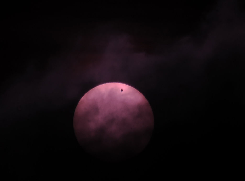 Venus is seen as a dot as it transits across the Sun on June 6, 2012 outside Sarajevo.
