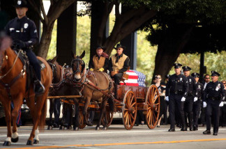 The casket carrying the remains of 45-year-old Los Angeles police SWAT officer and Marine reservist Robert J. Cottle is carried in a mule-drawn funeral wagon to services at the Cathedral of Our Lady of the Angels on April 13, 2010 in Los Angeles, California. Cottle and fellow Southern California Marine, 19-year-old Lance Cpl. Rick J. Centanni, of Yorba Linda, died when the armored vehicle they were in struck an improvised explosive device in the Marja region of Afghanistan during a US-led offensive against Taliban forces in the region. Cottle leaves behind a wife and a 9-month-old daughter and will be buried at Arlington National Cemetery.