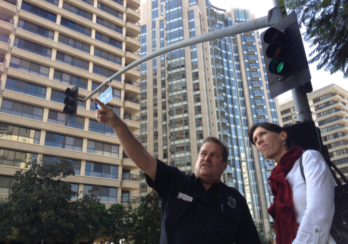 L,A. City Fire Inspector Molina  points out older high-rise buildings without fire sprinklers to KPCC's Karen Foshay at Wilshire Blvd. and Selby Ave.