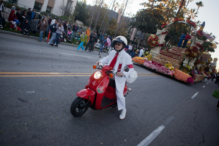 A Rose Parade volunteer leads a float along Orange Grove in front of the Tournament of Roses headquarters on Monday morning,