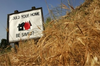 Dry grasses surround a sign in Kagel Canyon that encourages home owners to clear vegetation that could fuel a wildfire from around their properties near Los Angeles, California.