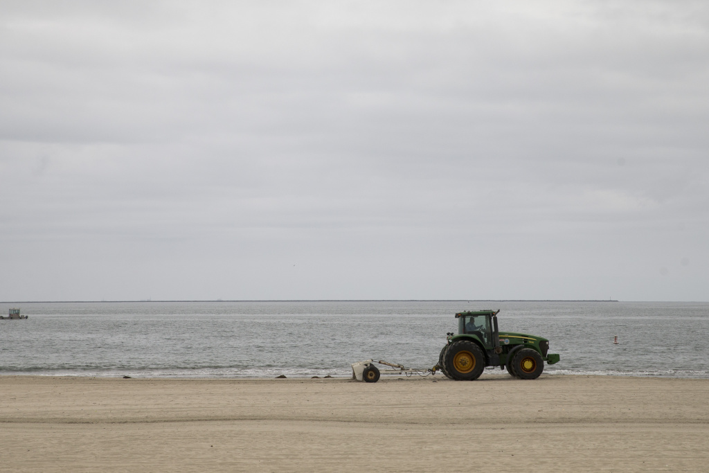 A tractor rakes up the debris on the beach, Thursday, June 4, 2015, in Long Beach, Calif.  A 4-mile stretch of a Los Angeles-area beach was closed Thursday to swimmers and surfers after tar balls washed ashore — the latest Southern California coastline to shut down due to oily goo, authorities said.