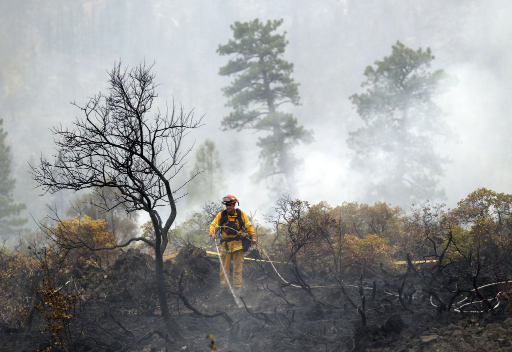 A firefighter with the Anderson, Calif., Fire Protection District douses hot spots left behind by the Eiler Fire along Highway 89 on Monday, Aug. 4, 2014, near Burney, Calif. Firefighters were focusing on two wildfires near each other in Northern California that have burned through more than 100 square miles of terrain.