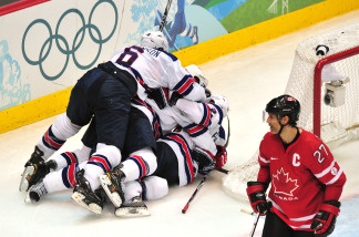 US players celebrate next to Canada's defender Scott Niedermayer at the end of the Men's preliminary Ice Hockey match Canada against USA at the XXI Winter Olympic games in Vancouver's Canada Hockey Place on February 21, 2010. USA won 5-3.