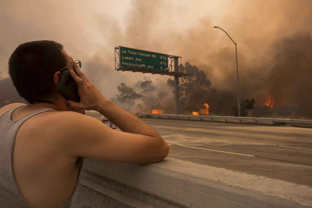 A man watches to see if his house and two of his cats on the other side of thick smoke and flames might burn near the community of Tujunga during the La Tuna Fire on September 2, 2017.