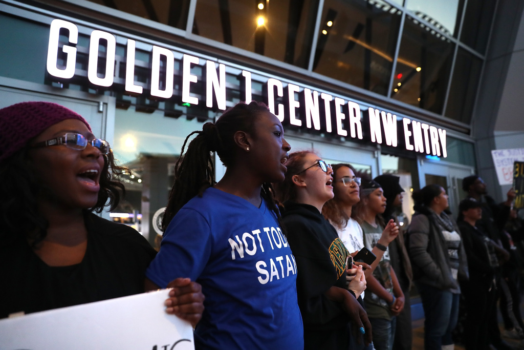 Black Live Matter protesters chant as they block the entrance to the Golden 1 Center during a demonstration on March 22, 2018 in Sacramento.