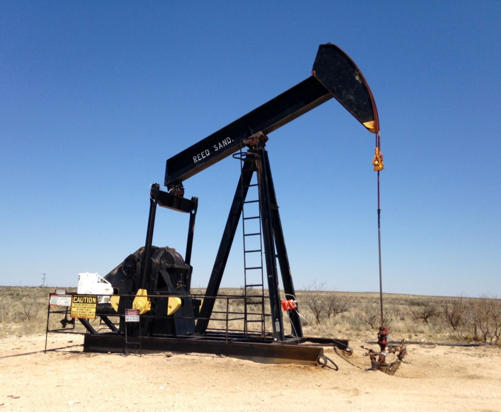 An older vertical pump jack sucks up crude oil outside Hobbs, New Mexico.