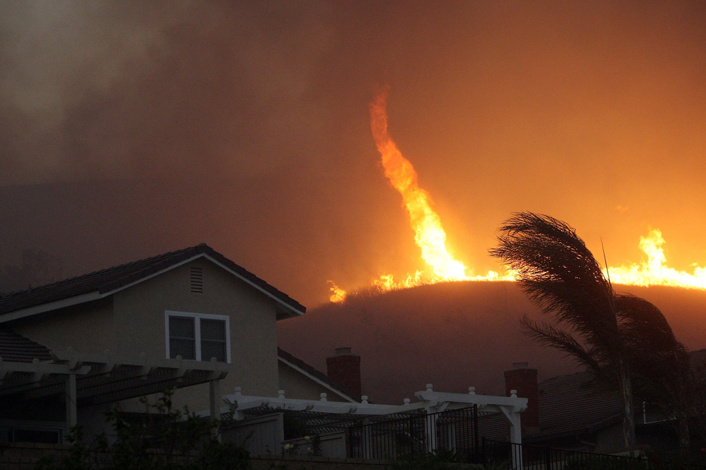 A fire tornado comes close to homes during the Corona Fire on November 15, 2008 in Yorba Linda, California. A new housing project was just approved for an area that burned during this fire.