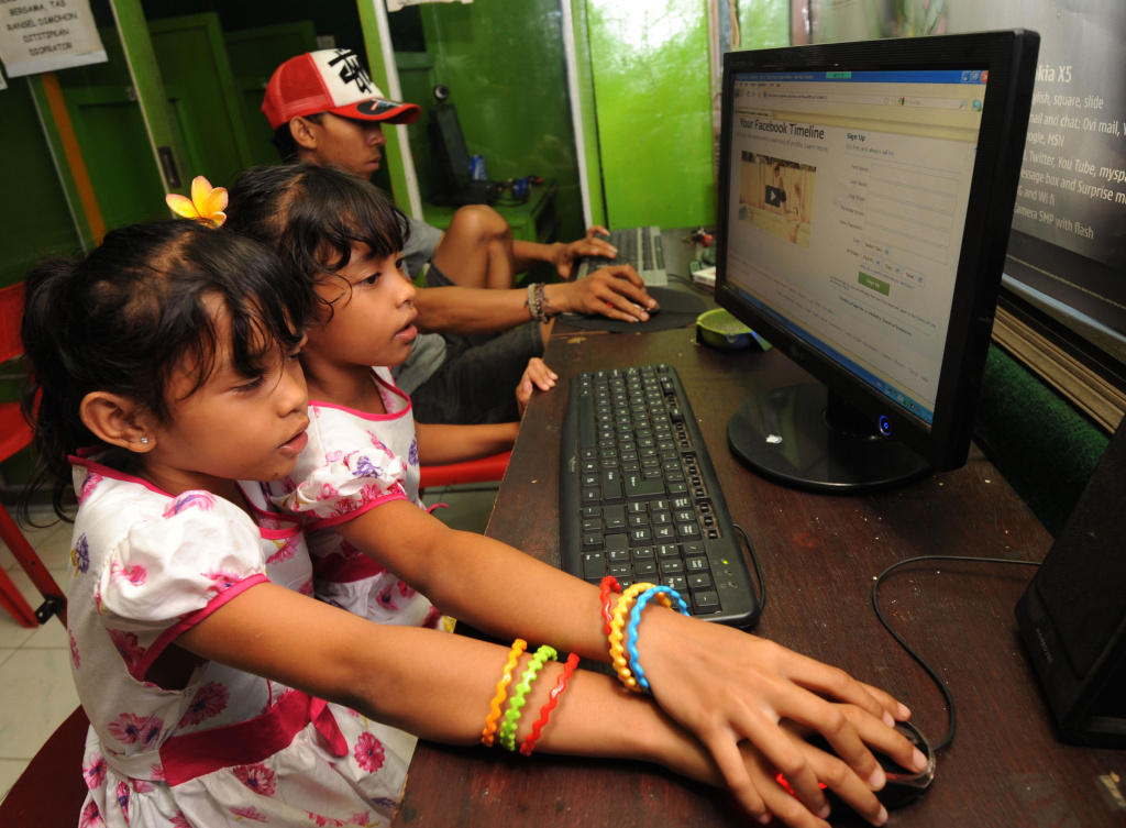 In this photograph taken Februay 2, 2012, Indonesian children log on a Facebook page at an internet shop in Kuta in the resort island of Bali. Indonesia, a developing Muslim nation which claims the world's third-largest community of Facebook users, has become a showcase for the social networking site's global reach.