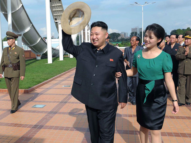 North Korean leader Kim Jong Un, accompanied by his wife, Ri Sol Ju, waves to the crowd as they inspect the Rungna People's Pleasure Ground in Pyongyang on July 25, 2012 in this photo released by the Korean Central News Agency. For North Koreans, it was stunning to see the first lady at the leader's side — and holding his arm.
