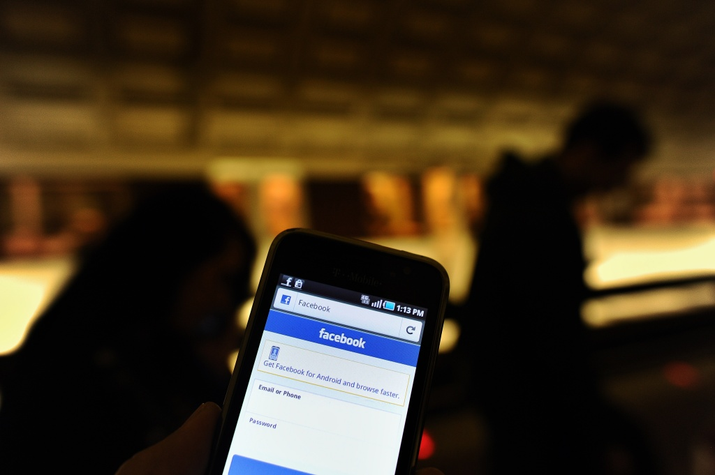 A man checks facebook on his smartphone while waiting for a train in a metro station in Washington, DC, on May 9, 2012.
