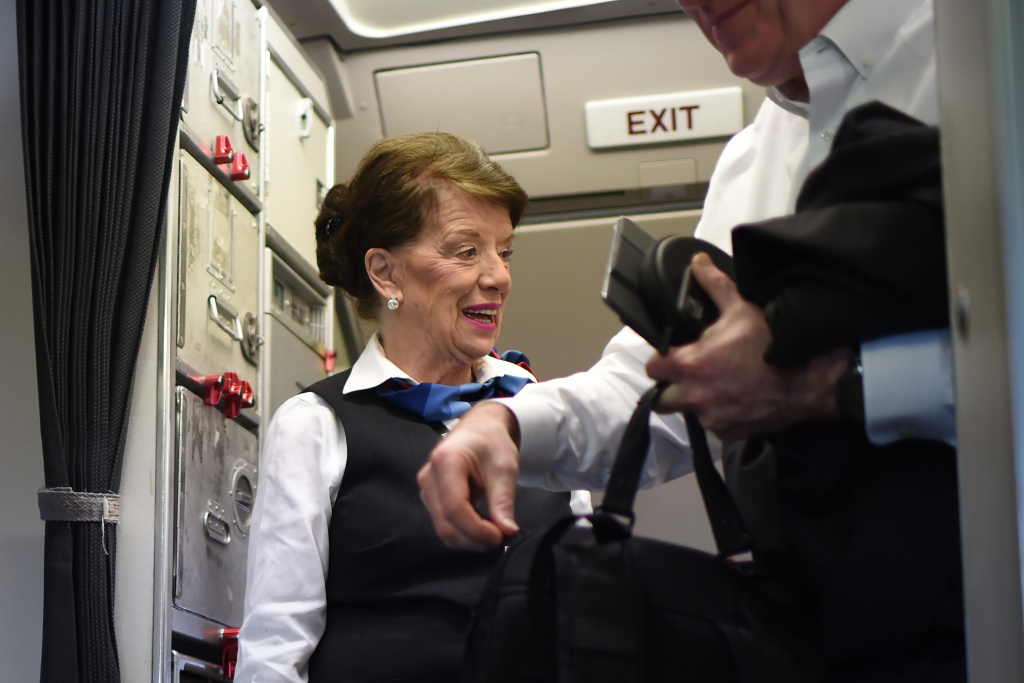 American Airlines longest serving flight attendant, Bette Nash (L), 81 years old, greets passengers disembarking from her daily return flight to Boston at Ronald Reagan Washington Airport in Arlington, Virginia on December 19, 2017.
