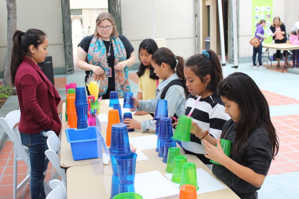 Children's librarian Brooke Sheets (center) uses colored cups to teach algorithms and debugging to a group of girls at a computer science fair at L.A.'s downtown Central Library