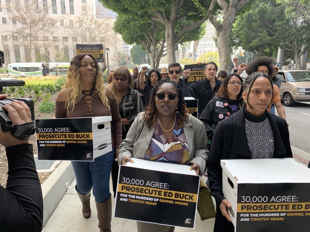 Community organizers including LaTisha Nixon, left, the mother of Gemmel Moore, carry boxes of signatures to the Hall of Justice.