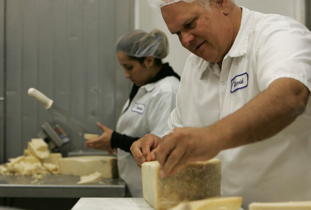 David Snyder hand cuts a wheel of cheddar cheese at the Fiscalini Cheese Co. October 26, 2006 in Modesto, California. California is poised to surpass Wisconsin as the top U.S. cheese producer by churning out 2.14 billion pounds of cheese last year, just shy of Wisconsin's 2.4 billion pounds.