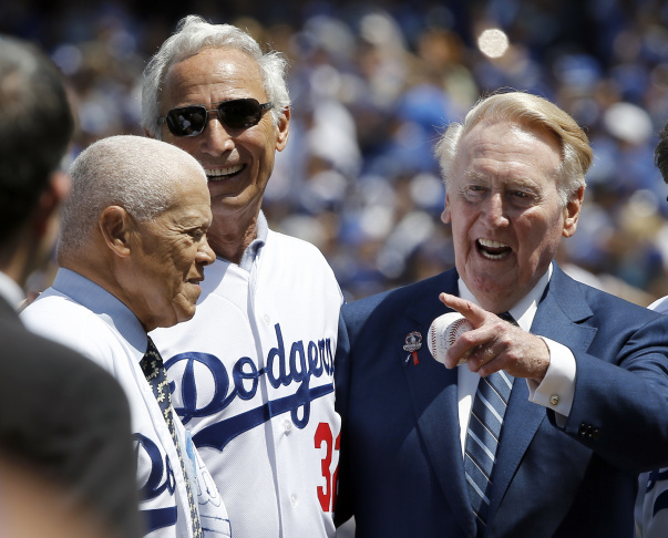 Los Angeles Dodgers broadcaster Vin Scully, right, points to another former player, with Sandy Koufax, center, and Maury Wills, left, before the start of an opening day baseball game between the Los Angeles Dodgers and Arizona Diamondbacks in Los Angeles, Tuesday, April 12, 2016. (AP Photo/Alex Gallardo)